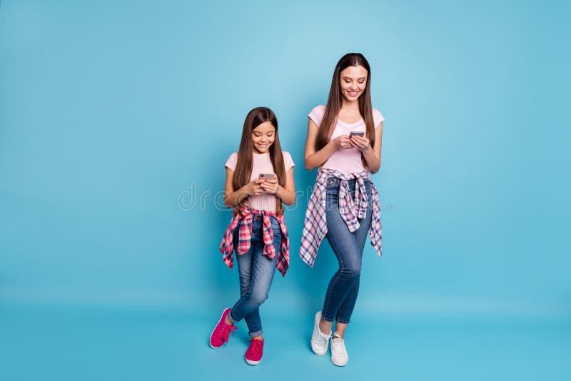 Körpergrößen-Ansichtporträt in voller Länge von zwei netten reizend attraktiven netten heitren gerad-haarigen Mädchen, die Intern stockfotos
