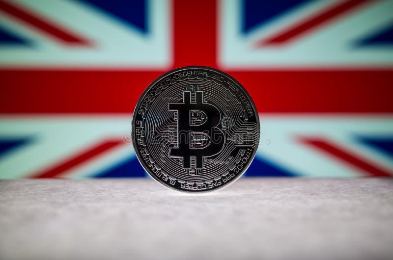 Körperliche silberne Version von Bitcoin BTC und von Flagge Vereinigten Königreichs auf dem Hintergrund Begriffsbild für Investor stockfotos
