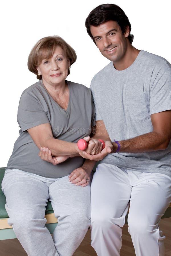 Körperlicher Therapeut, der einem Patienten hilft lizenzfreies stockbild