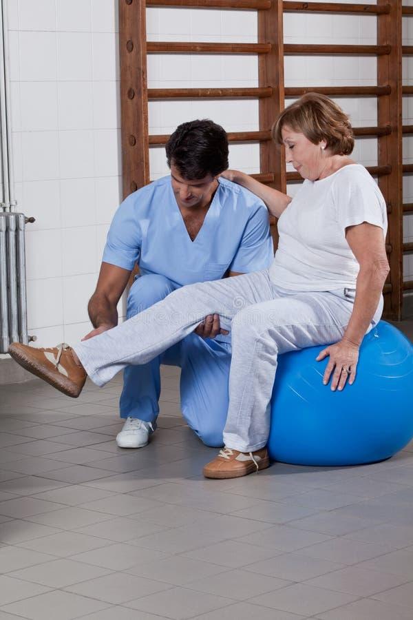 Körperlicher Therapeut, der einem Patienten hilft stockfoto