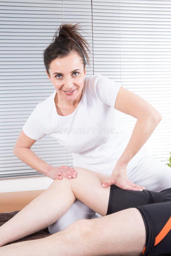 körperlicher Therapeut der Frau, der Massage des Sportmannbeines tut lizenzfreies stockbild