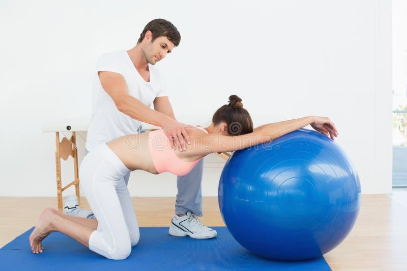 Körperlicher Therapeut, der Frau mit Yogaball unterstützt lizenzfreie stockfotos