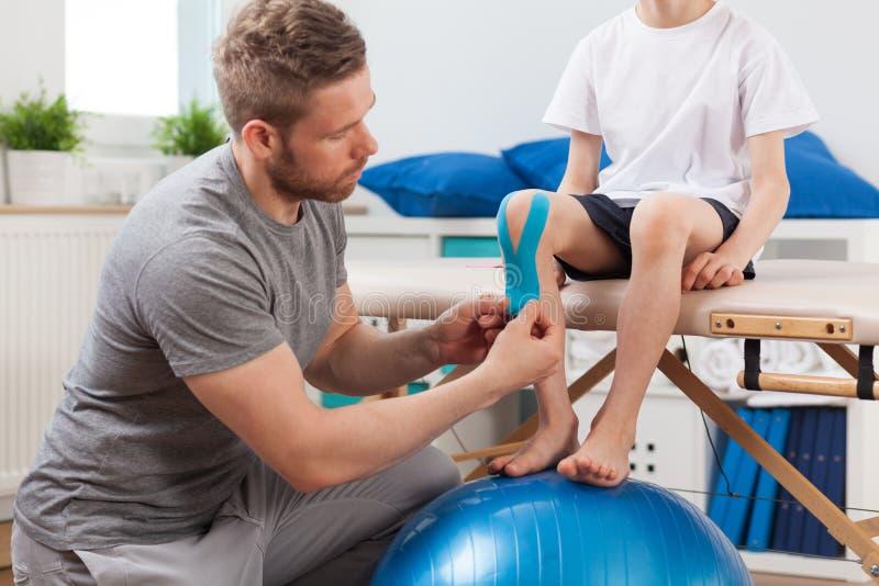 Körperlicher Therapeut, der Heftpflaster anbringt lizenzfreies stockfoto