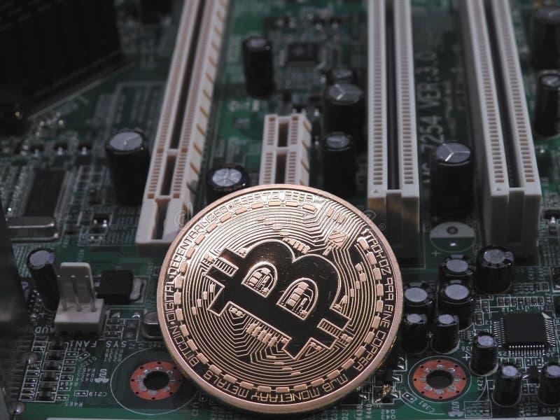 Körperliches bitcoin auf Computermotherboard lizenzfreies stockfoto