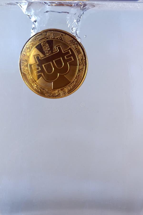 Körperliches bitcoin fallen gelassen in Wasser stockfotografie