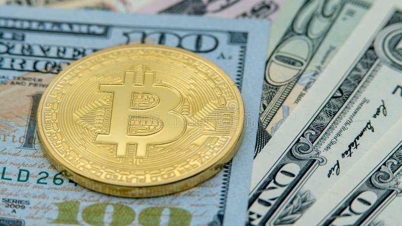 Körperliches Metallgoldene Bitcoin-Währung über amerikanischen Dollarscheinen btc stockfotografie