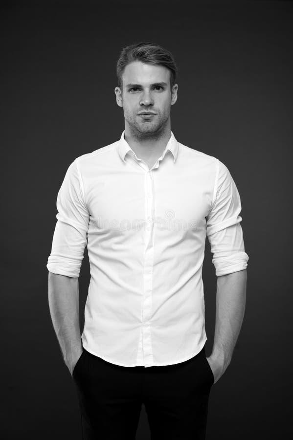 Körpersprache Was bedeutet, als Mann Hände in Taschen einsetzte Mann hübsch in den formalen weißen Hemdgriffhänden in den Taschen lizenzfreies stockfoto