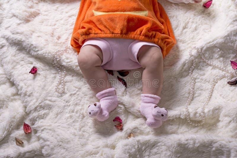 Körperteile eines Babys mit orange Strickjacke und rosa Hose auf w stockbilder