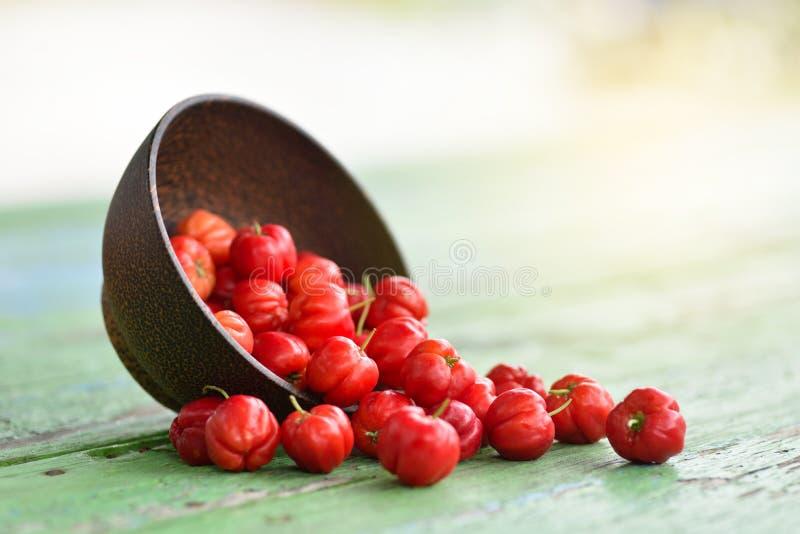 Körsbär för Acerola för bästa sikt för lägenhet lekmanna- röd i träbunke royaltyfria bilder