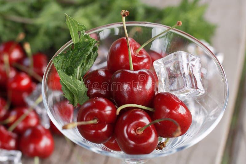 Körsbär i en närbild för exponeringsglasexponeringsglasexponeringsglas mot en trätabell som ligger på många körsbär och mintkaram arkivfoton