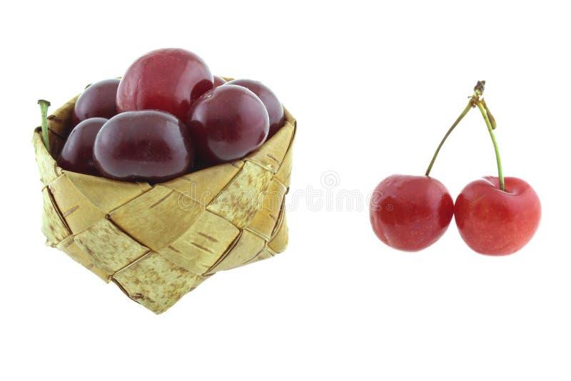 Körsbär i vide- korg och helhet som isoleras på vit bakgrund royaltyfri fotografi