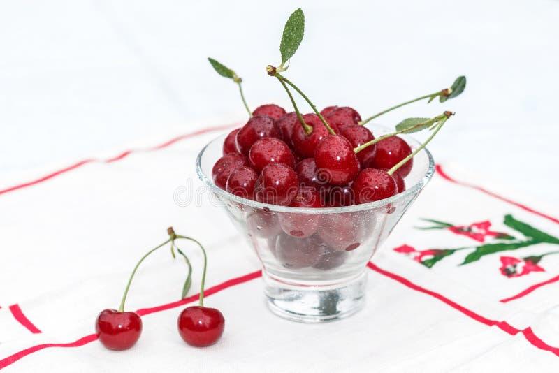Körsbär med vattendroppar i exponeringsglaset arkivbild