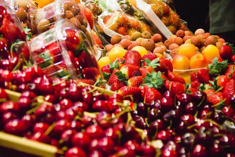 Körsbär och jordgubbar bär frukt i en marknad i barcelona Spanien royaltyfri foto