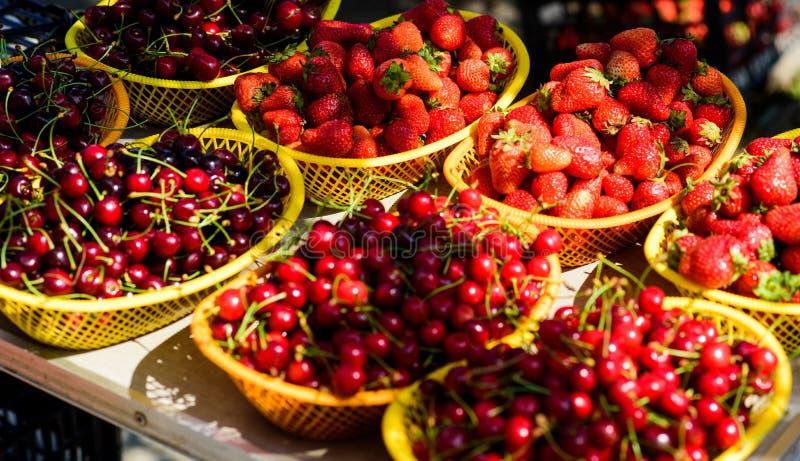 Körsbär och jordgubbar i korgar för försäljning Lantg?rdmarknad Röda mogna bär för sommarskörd Saftiga bär från trädgård royaltyfri foto
