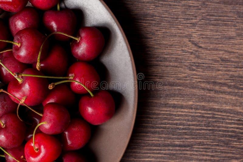 Körsbär på en platta, på en träbakgrund Sommarpicknicken, skörd, behandlar Mat för vegetarian och strikt vegetarian Riktig näring royaltyfri foto