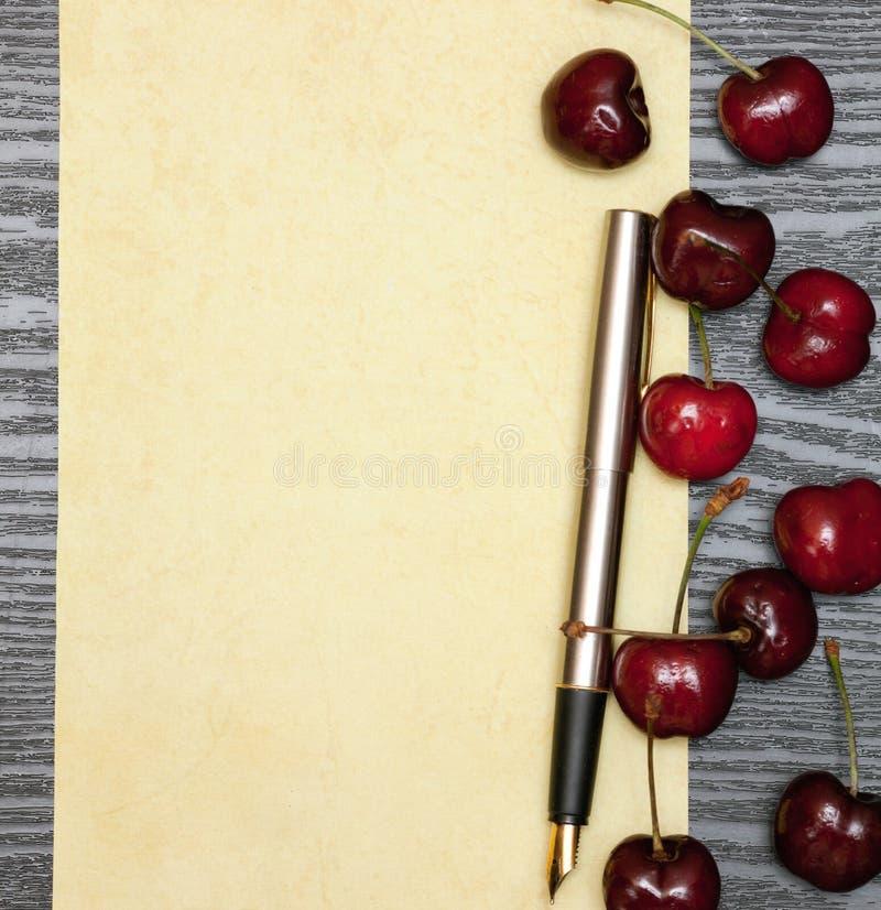 Körsbär på ett ark av papper arkivbild