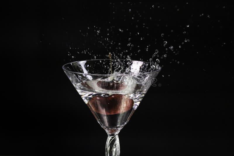 Körsbär som faller in i vatten, plaskande vinexponeringsglas royaltyfria foton
