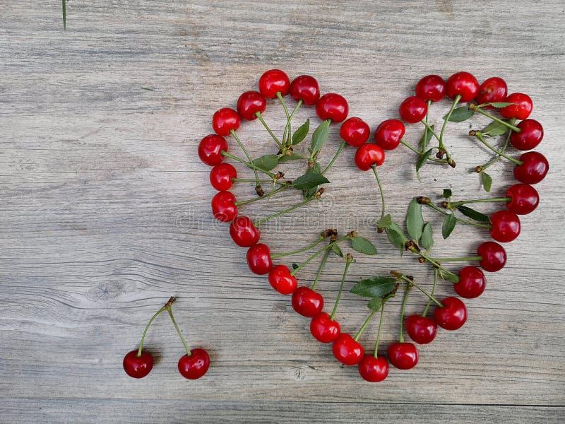 Körsbärsröd frukt för sommar för förälskelsehjärtabakgrund royaltyfri foto