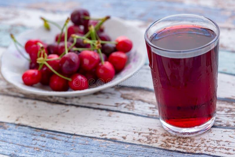 Körsbärsröd fruktsaft med körsbär i platta på turkostabellen royaltyfri bild