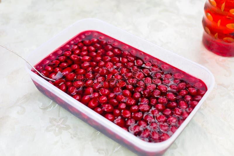 Körsbärsröd geléefterrätt med nya bär i fyrkantig matbehållare arkivfoton