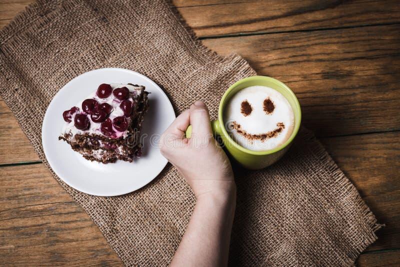 Körsbärsröd kaka med kaffe på träbakgrund royaltyfria foton