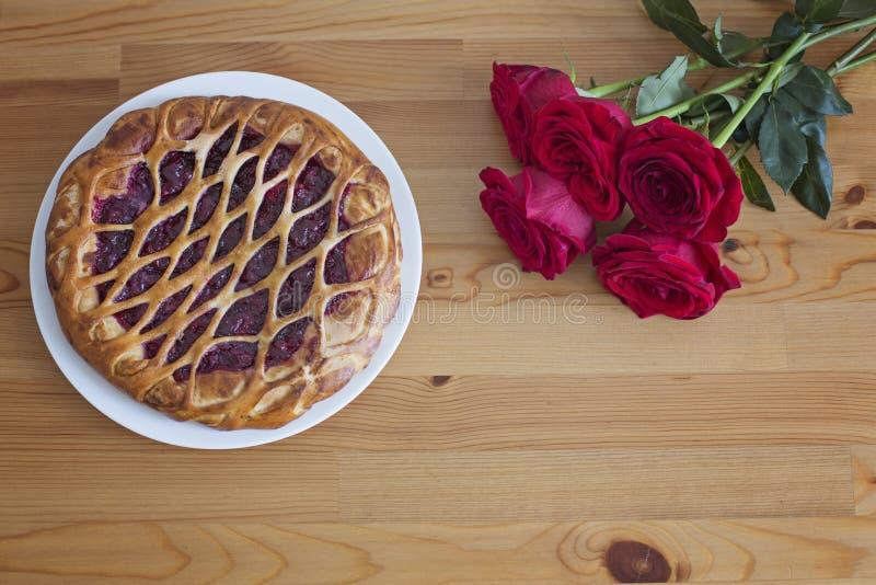 Körsbärsröd paj på en trätabell och en bukett av röda rosor arkivbild