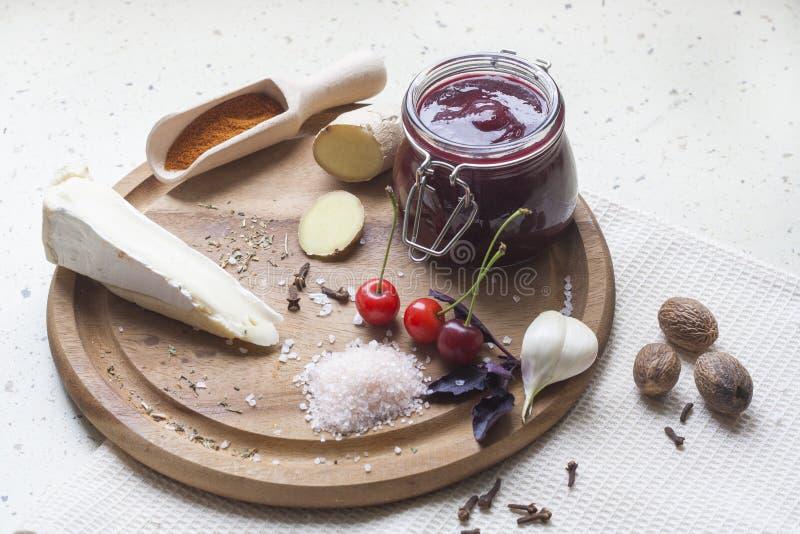 Körsbärsröd sås med den ostbrien, körsbäret och kryddan på träbräde royaltyfri bild