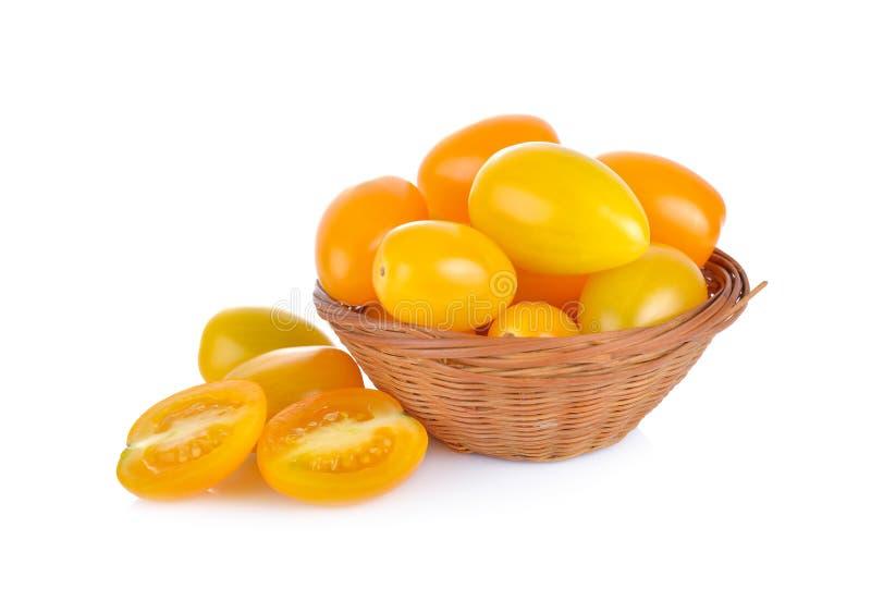Körsbärsröd tomat för helhet och för halv snittguling i bambukorg och på arkivfoton