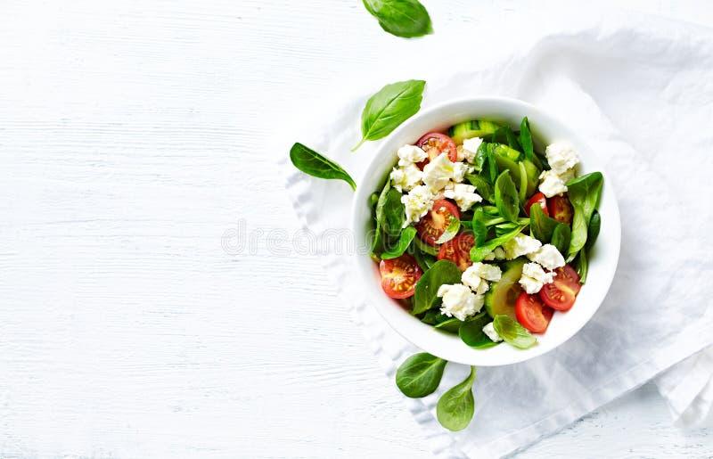 Körsbärsröd tomat, havregrönsallat och gurkasallad med feta kopiera avst?nd Lekmanna- l?genhet arkivbild