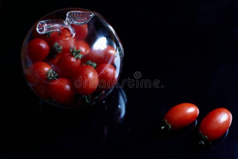 Körsbärsröd tomat i denShape flaskan arkivfoto