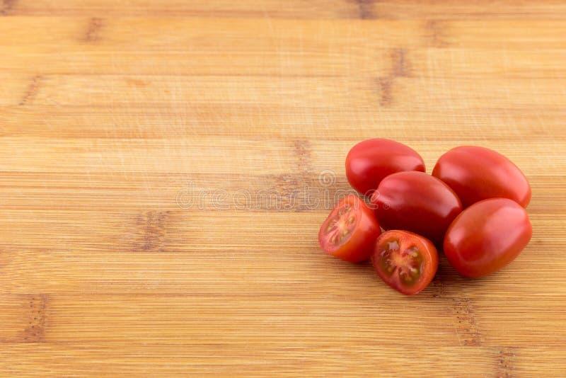 Körsbärsröd tomat på träbräde arkivbild