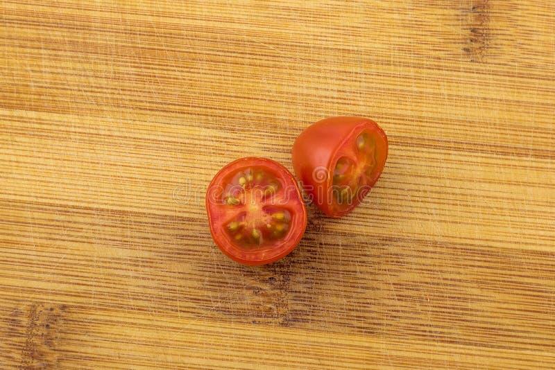 Körsbärsröd tomat på träbräde royaltyfri fotografi