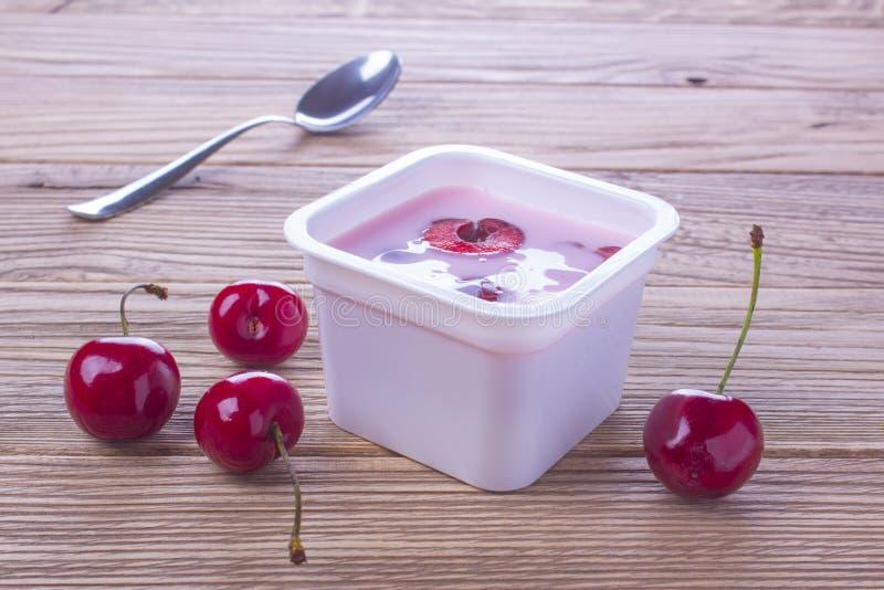 Körsbärsröd yoghurt i plast- ask med skeden royaltyfri bild
