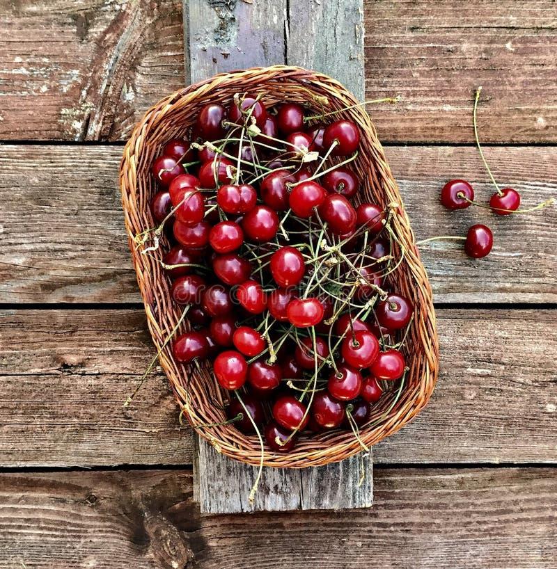 Körsbärsröda bär i en korg i stilen av lantligt arkivbild