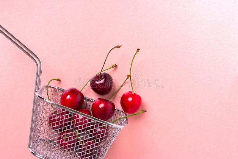 Körsbärsröda bär i en mini- korg för stål arkivbild