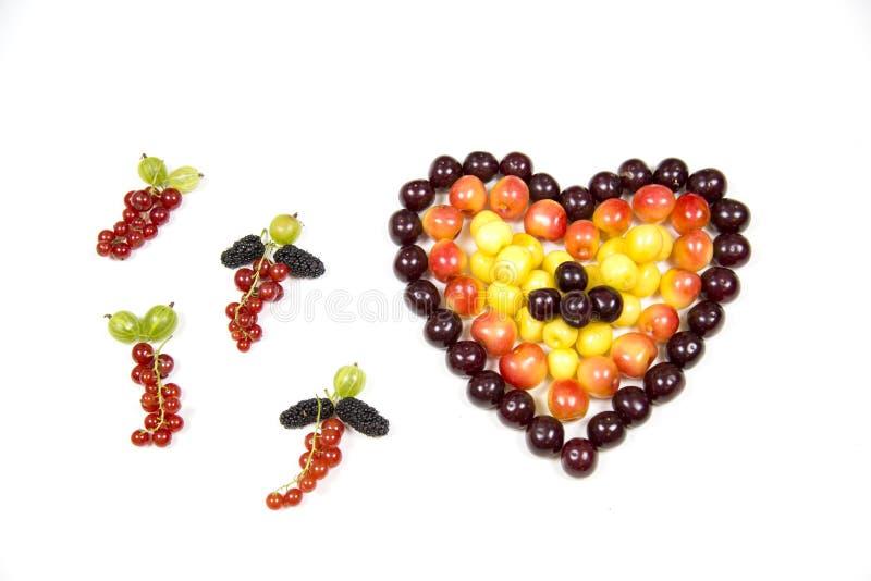 Körsbärsröda bärkörsbär i form av en hjärta av röd rosa guling och tofsar av krusbärmullbärsträdet för röd vinbär som isoleras på arkivfoto