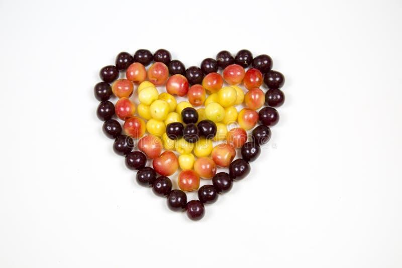 Körsbärsröda bärkörsbär i form av en hjärta av röd rosa guling som isoleras på en vit bakgrund, ett ställe för texten av det conc arkivfoto