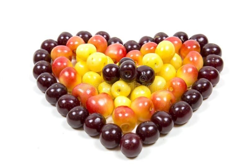 Körsbärsröda bärkörsbär i form av en hjärta av röd rosa guling som isoleras på en vit bakgrund, ett ställe för texten av det conc arkivbilder