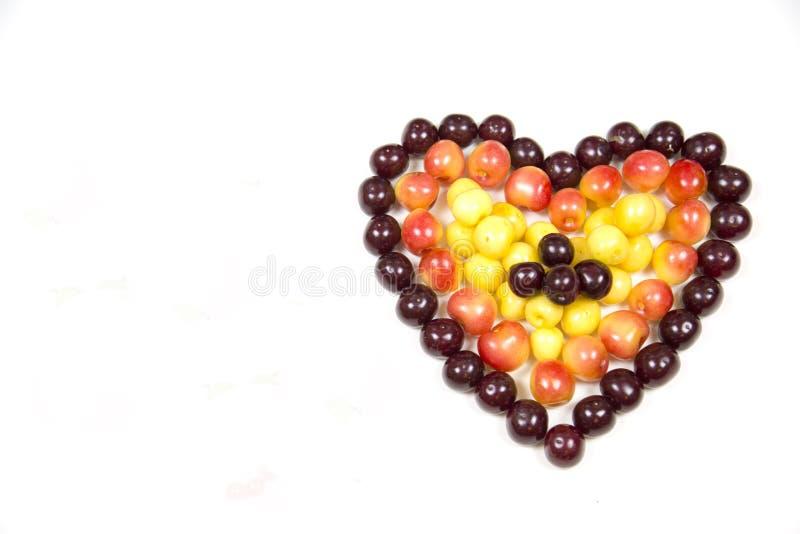 Körsbärsröda bärkörsbär i form av en hjärta av röd rosa guling som isoleras på en vit bakgrund, ett ställe för texten av det conc royaltyfri foto
