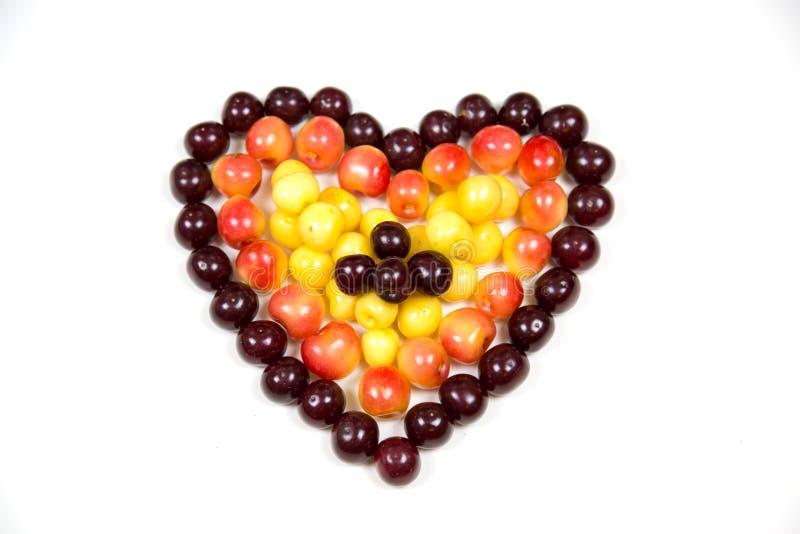 Körsbärsröda bärkörsbär i form av en hjärta av röd rosa guling som isoleras på en vit bakgrund, ett ställe för texten av det conc royaltyfria foton