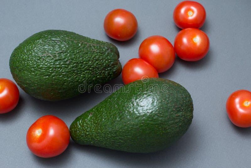 Körsbärsröda tomater för avokado arkivfoto