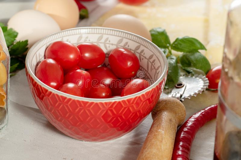 Körsbärsröda tomater i en liten röd bunke royaltyfria bilder