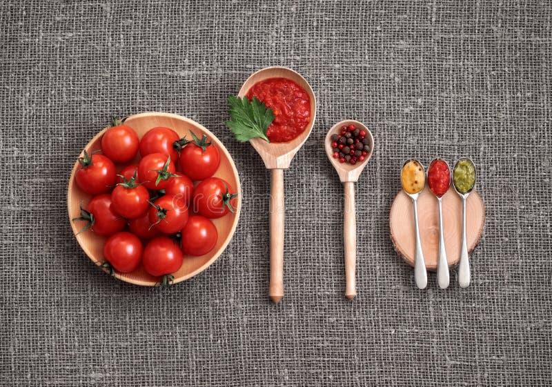 Körsbärsröda tomater i en träplatta på en grå bakgrund Adjika sås, rött och svartpeppar, persilja, senap och pesto i skedar royaltyfri bild