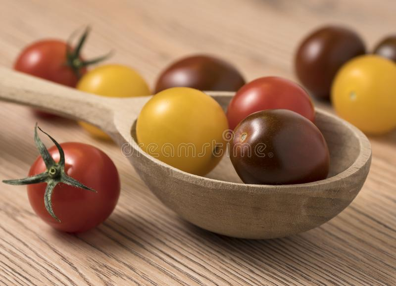 Körsbärsröda tomater i en variation av färger i träsked royaltyfri fotografi