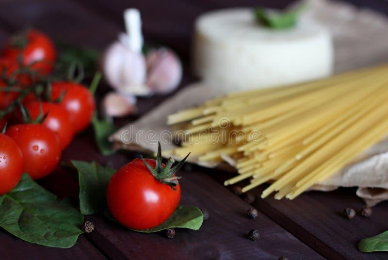 Körsbärsröda tomater, italiensk pasta, vitlök, spenat, peppar på mörk wood bakgrund royaltyfria foton
