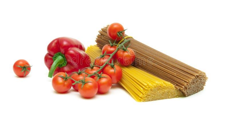 Körsbärsröda tomater, peppar och pasta som isoleras på vit bakgrund royaltyfria foton