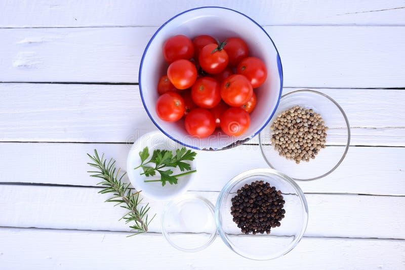 Körsbärsröda tomater, peppar, persilja, rosmarin och saltar på vitbac royaltyfri fotografi