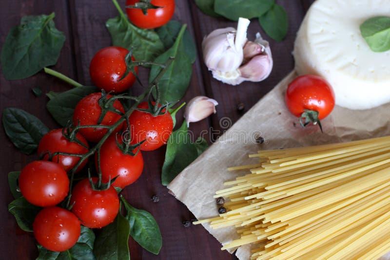Körsbärsröda tomater, rå pasta, vitlök, spenat på mörk wood bakgrund royaltyfri foto