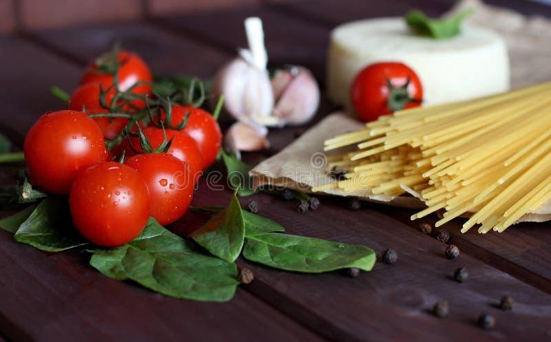 Körsbärsröda tomater, rå pasta, vitlök, spenat på mörk wood bakgrund royaltyfri bild