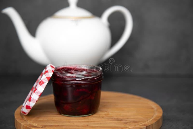 Körsbärsrött driftstopp, driftstopp, gelé i en exponeringsglaskrus med ett rött och vitt lock bredvid ett trärunt bräde, bräde Mo royaltyfria bilder